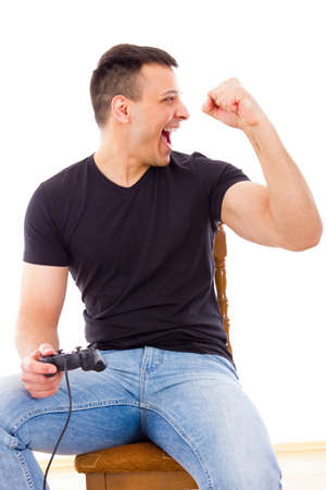 sexy man in jeans winning video game playing with joystick photo