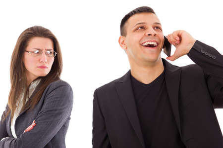 unfaithful: jealous suspicious woman looking at unfaithful man talking with somebody on the mobile Stock Photo