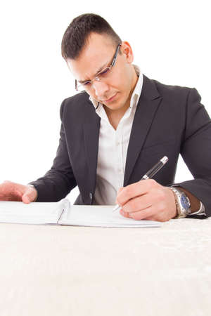 concentrated thoughtful professor with glasses writing evaluation and adding reviews Stock Photo