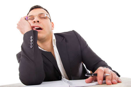 exhausted businessman sleeping at his desk yawning with pencil in hand