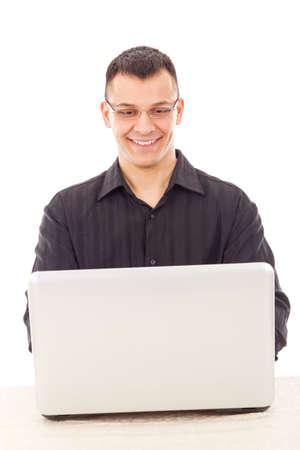 white laptop: bell'uomo sorridente con gli occhiali in una camicia nera che esamina computer portatile bianco Archivio Fotografico