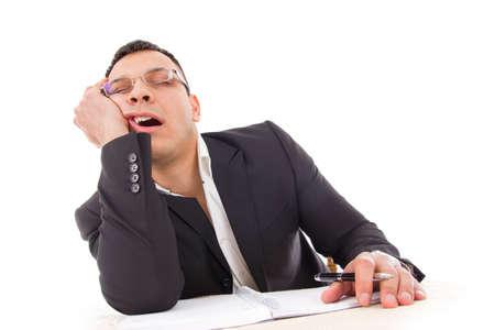 perezoso: hombre de negocios cansado bostezo y durmiendo en el trabajo con la pluma en la mano