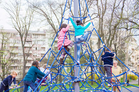 little children climb on the jungle gym at the park