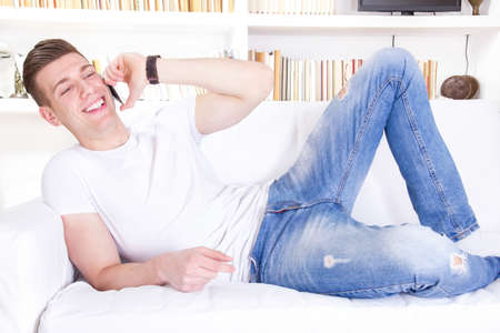 happy smiling young man talking on mobile relaxing on sofa at home photo
