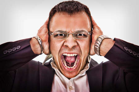 businessman with glasses grabbing his head and yells photo