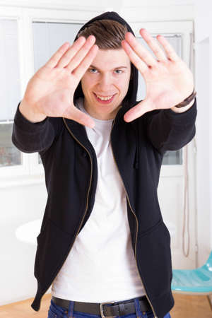 cool young guy in hooded black jacket framing his face with hands photo