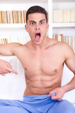 homme nu: moitié surpris homme nu pointant un doigt vers le bas à l'aine