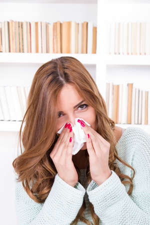 beautiful girl feeling ill caught cold sniffles blowing her nose into tissue photo
