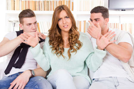 confused and doubtful beautiful woman hasitates between two young guys photo