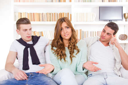 unsure pretty confused and doubtful woman choosing between two young men photo