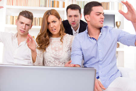 young frustrated casual group of friends sitting on couch looking at laptop, pissed off friends, cheering on computer