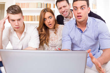 shocked and frustrated casual group of friends sitting on couch looking at laptop, pissed off friends, cheering on computer