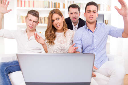 frustrated and shocked casual group of friends sitting on couch looking at laptop, pissed off friends, cheering on computer Stock Photo