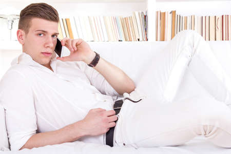 seductive young man lying on sofa talking on the phone dressed in white photo