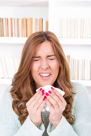 sick woman sniffles with flu virus feeling ill sneezing into tissue photo