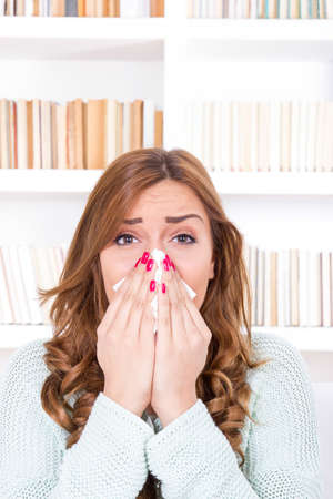beautiful sick woman with cold and virus sneezing into tissue photo