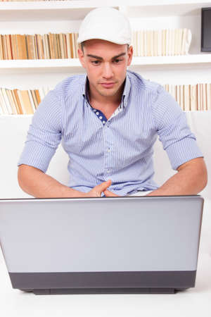 young fashion man wearing shirt and cap looking at computer monitor in front of book shelf