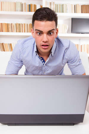 concerned business man looking at computer monitor shocked
