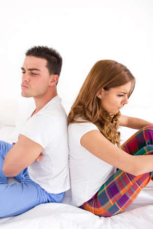 angry and upset couple in fight turning their back on each other in bed, domestic bedroom atmosphere photo
