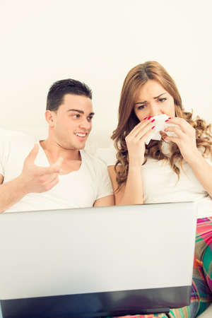 ordinary casual young couple in love watching sad movie in bed on laptop computer. Man smiling to a woman with a handkerchief while she is crying and shedding tears. Vintage effect style photo