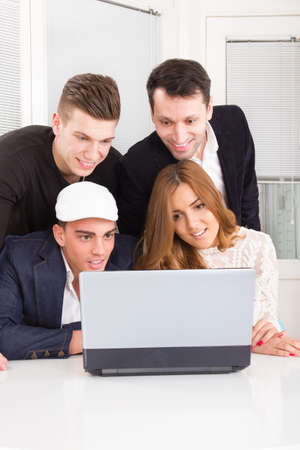 curious friends looking at laptop computer monitor together smiling. Business, technology and education concept photo