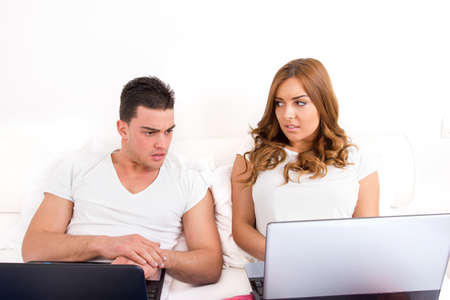 depressed and shocked young man looking at womans computer. Casual partners in bed with laptop computers. Caught in cheating on a social network photo