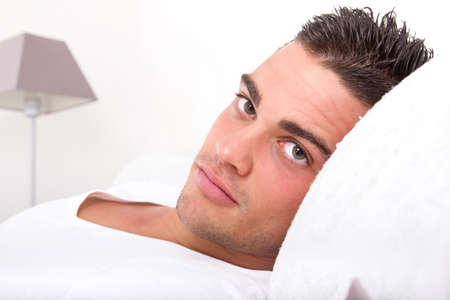 handsome sensual man lying in bed. Closeup face with seductive beautiful eyes looking at camera holding head on the pillow photo