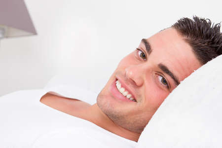 portrait of handsome sensual man smiling lying in bed with head on the pillow photo