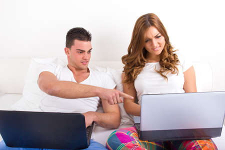 Couple with two laptop computers in bed. Man and woman both with computer, woman upset and surprised man looking at her computer. Young modern casual couple in bed. Caucasian man and woman. Funny image. photo