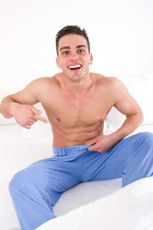 man in pajamas with problem in bedroom laughing at it, sexual dysfunction trouble photo
