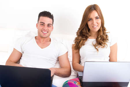 smiling couple with two laptop computers in bed. Man and woman both with computer. Young modern casual couple in bed. Caucasian man and woman. domestic happy image. photo