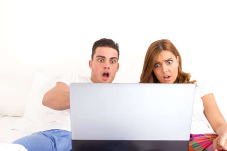 surprised casual young shocked couple in love watching tragic and dramatic horor movie in bed on laptop computer. People scared because scary scene in movie. Virus attacks Internet and social network photo