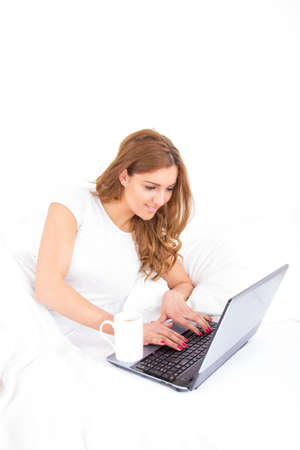 angle view of woman using laptop computer in bed with cup of coffee aside