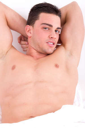 attractive muscular man lying in his bed smiling and seducing photo