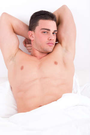 attractive muscular man lying in bed with naked torso awakening photo