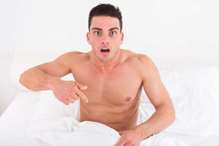 surprised and shocked half naked young man in bed  looking down at his underwear at his penis under white covers sheet in badroom. Concept photo of male sexuality and man sex problems, domestic atmosphere. photo