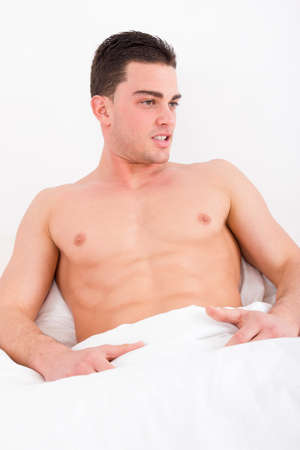 handsome man covered in white sheets with naked torso lying in bed photo