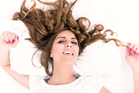 wavy hair: portrait of young casual woman lying in bed with hair spread around, domestic atmosphere