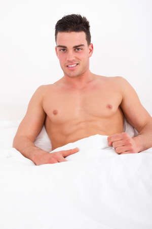 proud attractive man lying in bed with naked torso smiling covered with white sheets photo