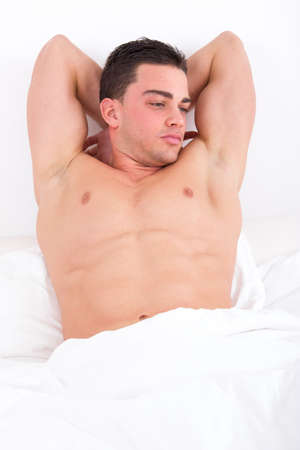 seductive pensive young man lying in bed with naked torso photo