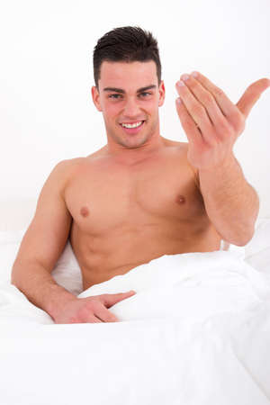 sexy man with naked torso calling you to come in bed, come here gesture photo