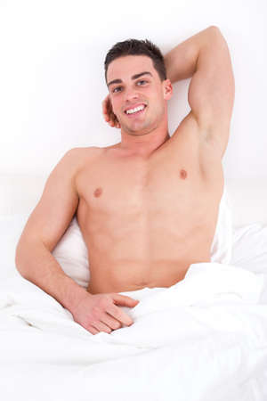 sexy man with naked torso lying on the bed smiling photo