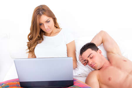 woman relaxing in bed using laptop while husband is sleeping; leisure couple photo