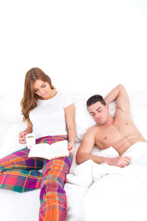 young couple in love relaxing in bed; girl reading book wih coffee in bed while man is sleeping next to her photo