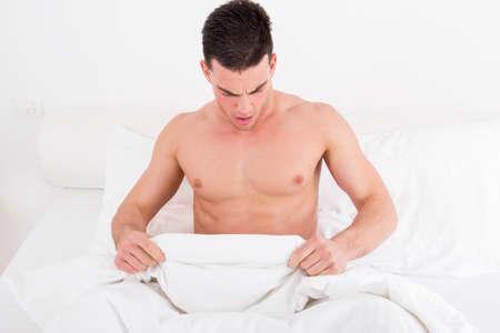 sex�: medio sorprendida joven desnuda en la cama mirando hacia abajo a su ropa interior en el pene bajo blanco cubre la hoja de ba�o fant�stico. Foto del concepto de los problemas de la sexualidad y del sexo del hombre macho, el ambiente dom�stico.