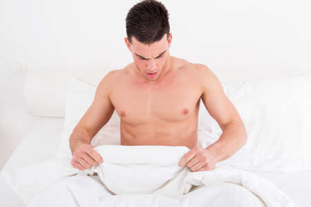 sex: surprised half naked young man in bed  looking down at his underwear at his penis under white covers sheet in badroom. Concept photo of male sexuality and man sex problems, domestic atmosphere. Stock Photo