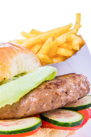 burger in bun with french fries and cucumber and tomato salad isolated in closeup photo