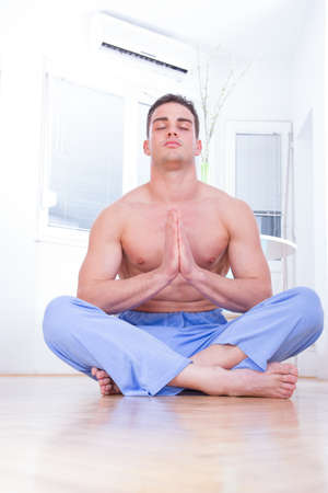 bare chested: good looking young handsome bare chested man doing yoga at his home indoors