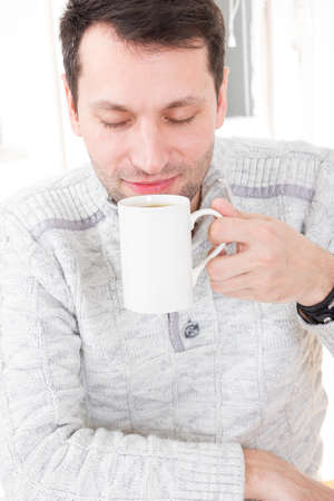 Morning portrait of handsome guy smelling and holding coffee cup wit eyes closed at his home indoors, domestic atmosphere