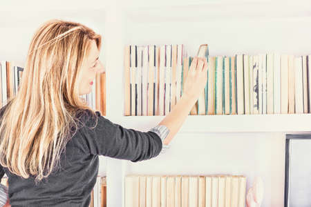 beautiful young woman taking a book from shelf in library, girl choosing a book from bookshelf, female student reaching for the book from top shelf